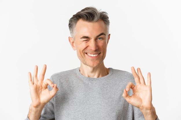 Primo piano di un uomo di mezza età bello e fiducioso, che mostra segni di ok