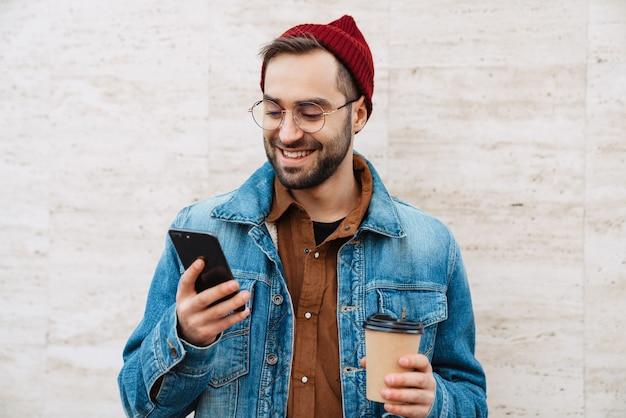 Primo piano di un bel giovane uomo barbuto elegante e felice che cammina all'aperto per strada, tenendo in mano una tazza di caffè da asporto, usando il telefono cellulare