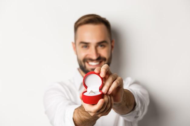 Primo piano di un bell'uomo che chiede di sposarlo, concentrarsi sulla scatola con anello nuziale, concetto di proposta e relazione, sfondo bianco