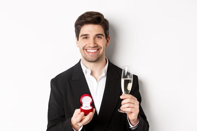 Primo piano di un bell'uomo in giacca e cravatta, che fa una proposta, dà l'anello di fidanzamento e alza un bicchiere di champagne, in piedi su sfondo bianco