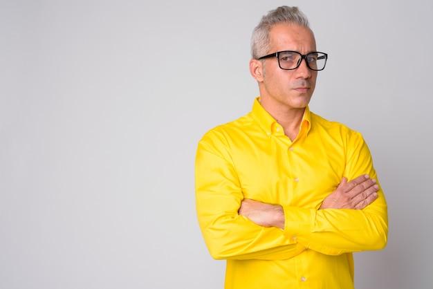 Chiuda in su dell'uomo d'affari persiano bello che porta camicia gialla isolata