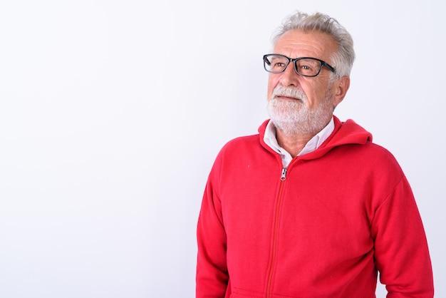 Chiuda in su dell'uomo barbuto anziano bello che pensa mentre cerca su bianco