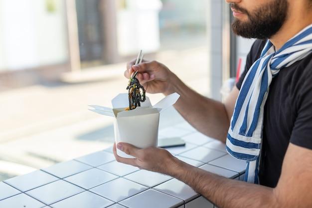 Primo piano del ragazzo giovane bello hipster che mangia tagliatelle cinesi usando le bacchette di legno che si siedono in un
