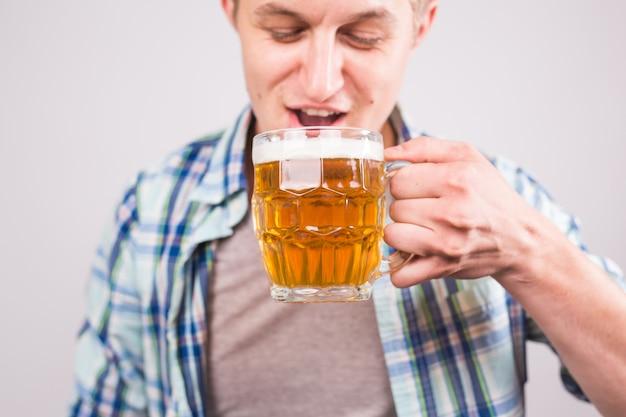 Primo piano della birra di prova del giovane bello.