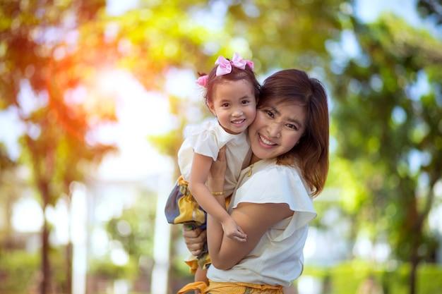 Chiuda sul fronte di felicità di sorridere asiatico a trentadue denti della piccola figlia e della madre asiatica all'aperto