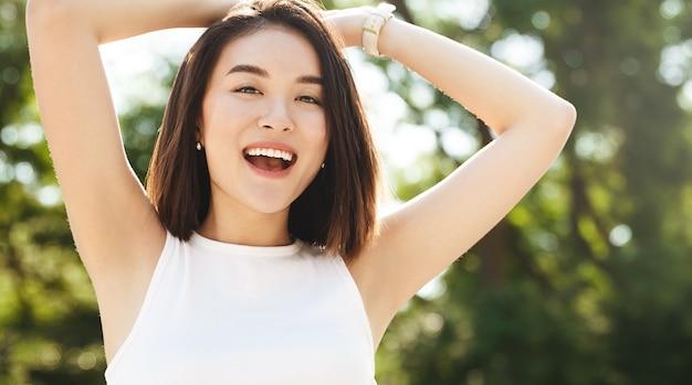 Primo piano della donna asiatica felice che posa nel parco, sorridente e che guarda l'obbiettivo, tenendosi per mano dietro la testa rilassata