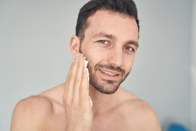 Primo piano di un maschio barbuto felice con un corpo muscoloso al momento di applicare la crema da barba sul viso