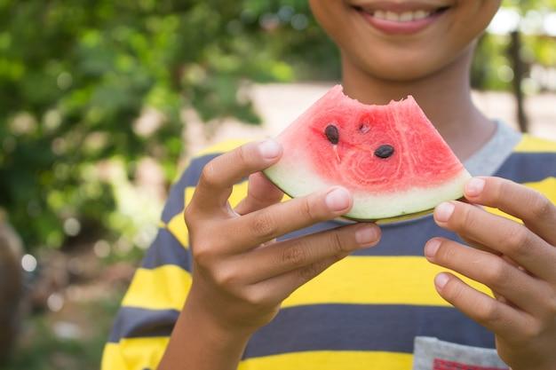 Primo piano di ragazzo felice è azienda anguria su sfondo verde della natura.