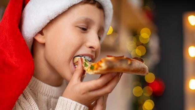 Primo piano di un ragazzo felice con santa cappello mangiare la pizza
