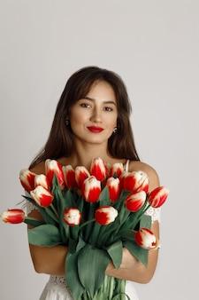 Chiuda sulla donna felice del brunette con gli orli rossi che tengono il mazzo dei tulipani e dello sguardo rossi