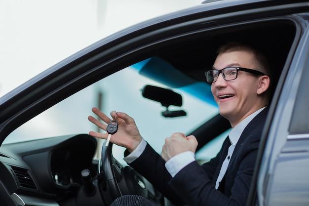 Avvicinamento. uomo d'affari felice che tiene le chiavi della sua nuova auto