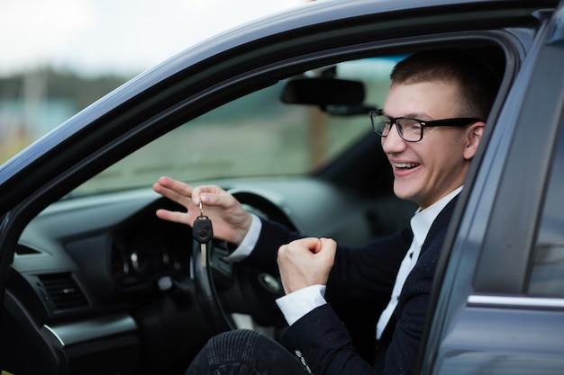 Avvicinamento. felice uomo d'affari seduto nella sua nuova auto e mostrando le chiavi