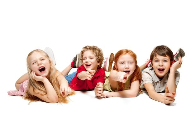 Primo piano di bambini felici sdraiati sul pavimento in studio e guardando in alto, isolati su sfondo bianco. emozioni per bambini, giorno del libro, educazione, scuola, bambino, conoscenza, infanzia, amicizia, concetto di studio