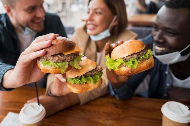 Amici felici del primo piano che tengono gli hamburger