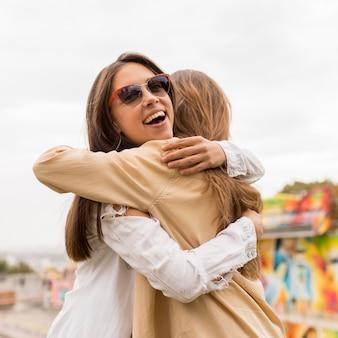 Amici felici del primo piano che abbracciano