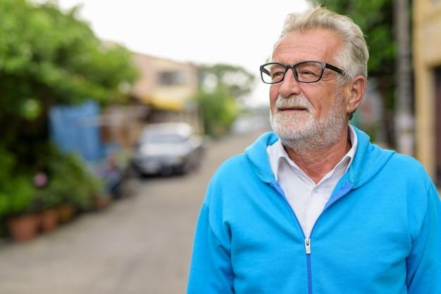 Close up felice bello senior uomo barbuto sorridente mentre pensa e indossa occhiali da vista e giacca blu all'aperto