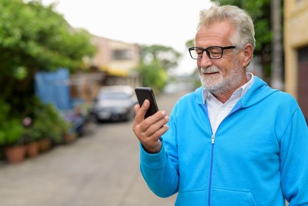 Close up felice bello senior barbuto uomo sorridente mentre si utilizza il telefono cellulare con gli occhiali all'aperto