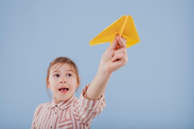Primo piano, una bambina felice tiene in mano un aeroplano di carta gialla, isolato su sfondo blu, copia spazio