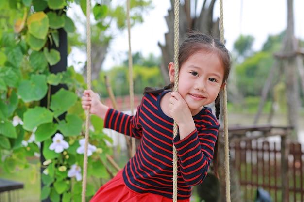 Chiuda sul piccolo gioco asiatico felice della ragazza del bambino e sedersi sull'oscillazione nel parco naturale.