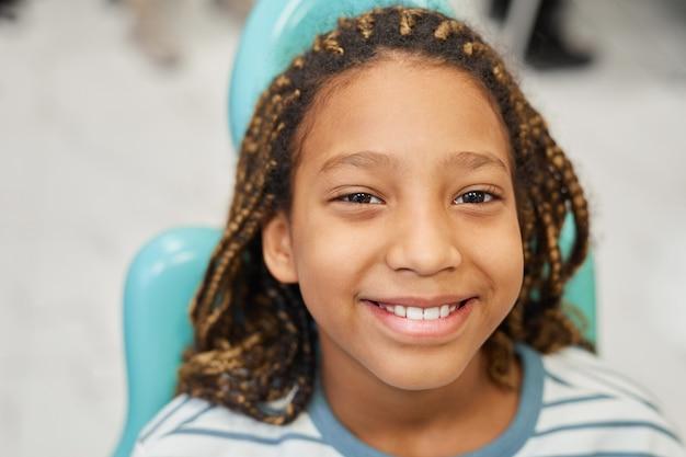 Close-up di felice bambina sorridente davanti mentre è seduto sulla poltrona odontoiatrica