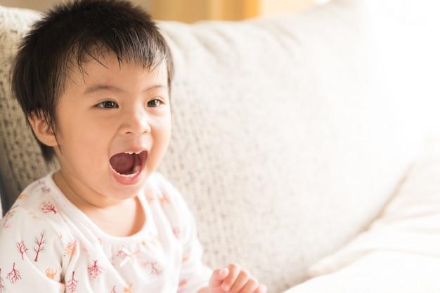 Chiuda sulla bambina felice che sorride e che ride la seduta sul sofà.