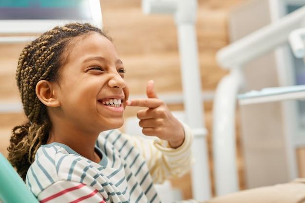 Primo piano del piccolo paziente felice che si siede sulla sedia dentale e che mostra i suoi denti sani