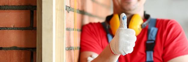 Primo piano del carpentiere maschio felice che mostra i pollici in su. lavoratore sorridente del cantiere che lavora al progetto. muro di mattoni rossi. ristrutturazione e concetto di costruttore professionale