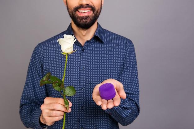 Chiuda in su della scatola di contenimento uomo felice con anello di nozze e rose