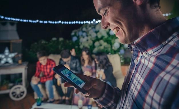 Primo piano di un uomo felice che guarda il suo smartphone in una festa all'aperto con gli amici. concetto di amicizia e celebrazioni.