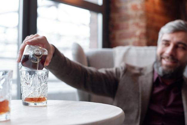 Primo piano dell'uomo felice che versa il whisky nel bicchiere mentre riposa nel lounge bar