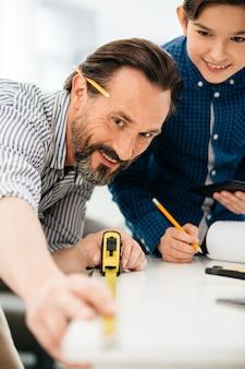 Primo piano di uomo felice utilizzando un metro a nastro e sorridente mentre si lavora al progetto emozionante con suo figlio positivo