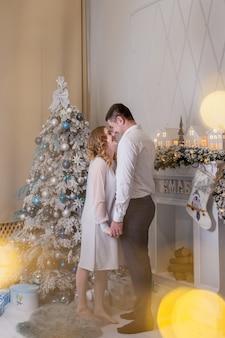 Chiuda in su del legame felice della coppia sposata accanto all'albero di natale. il miglior regalo di natale. la giovane donna incinta con suo marito decora l'albero di natale. una giovane coppia di innamorati in maglioni accoglienti.