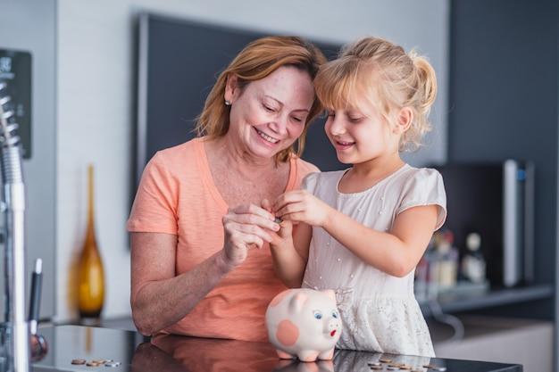 Primo piano felice madre anziana e adorabile piccola figlia che tiene toccante salvadanaio rosa, mamma premurosa e adorabile bambina che risparmia denaro per il futuro, l'assicurazione familiare e il concetto di investimento