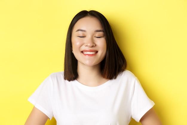 Primo piano di una ragazza asiatica felice e romantica che sogna qualcosa, chiude gli occhi e sorride felice, in piedi su sfondo giallo