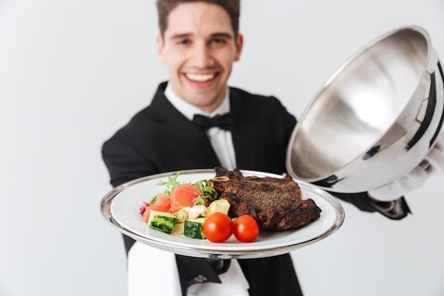 Chiuda in su di un cameriere felice che presenta un piatto di carne isolato sopra il muro grigio