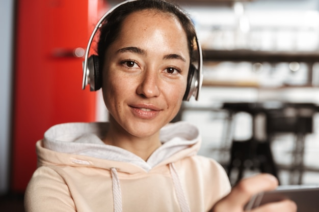 Primo piano di una donna felice che ascolta la musica con le cuffie a casa