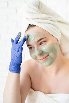 Chiuda in su di giovane donna caucasica felice in asciugamani da bagno bianchi che indossano guanti che applicano la maschera per il viso di argilla guardando allo specchio