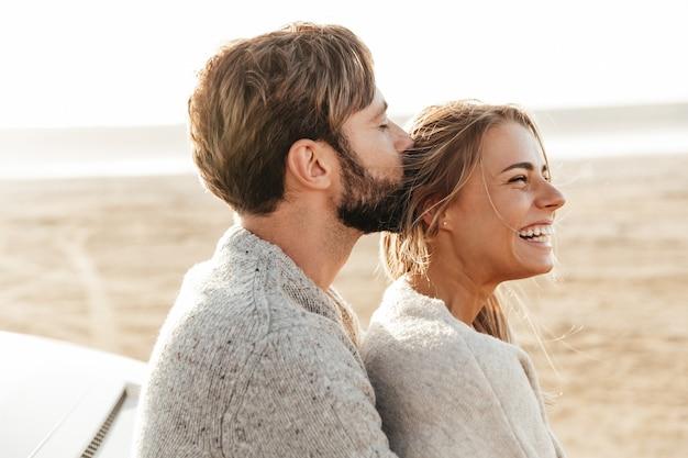 Primo piano di una giovane coppia felice innamorata che si abbraccia mentre si appoggia su un'auto sulla spiaggia soleggiata