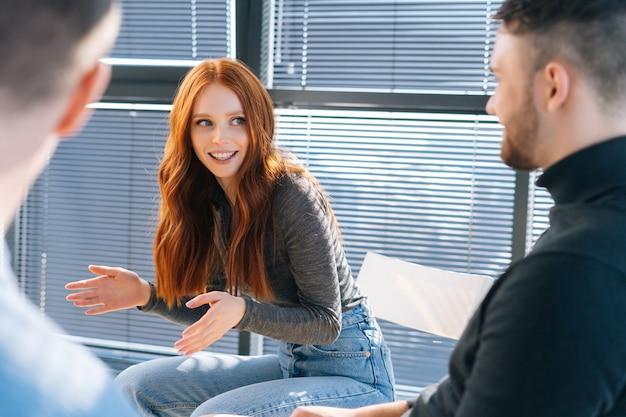 Primo piano di una giovane donna d'affari rossa felice che parla e discute di nuove idee con un team di business creativo, durante il brainstorming di progetti di avvio nella moderna stanza dell'ufficio vicino alla finestra.