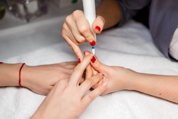 Chiuda in su della manicure dura in un salone di bellezza
