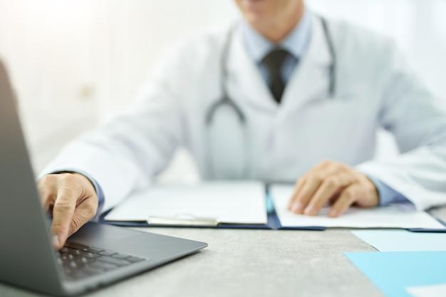 Primo piano dell'operatore sanitario seduto al tavolo con documenti e digitando sulla tastiera del notebook