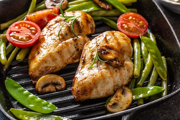 Close-up di sano cibo cucinato in casa, pollo alla griglia in una padella con verdure verdi, funghi e pomodori.