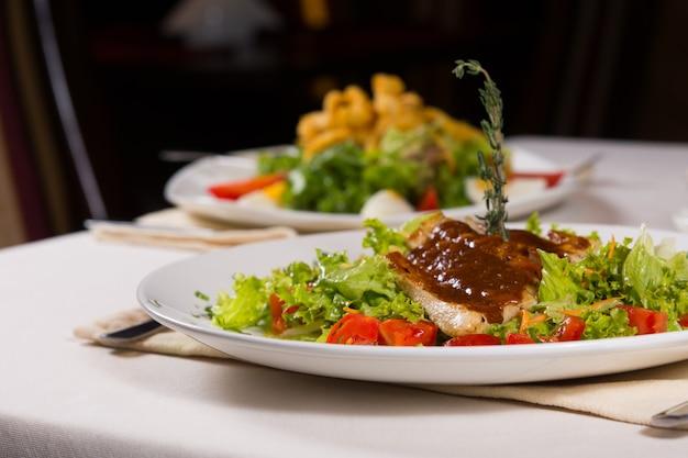 Primo piano sano piatto principale ricetta con carne e verdure su bianco piatto rotondo servito al ristorante durante la cena.