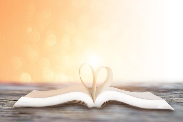 Primo piano a forma di cuore dal libro di carta su sfondo rosa bokeh, concetto di san valentino