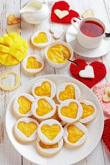Close-up di linzer biscotti a forma di cuore con marmellata di mango su un piatto bianco su un tavolo con tovaglioli a forma di cuore lavorati a maglia. una tazza di tè, mango a fette e una brocca con crema sul tavolo, vista verticale