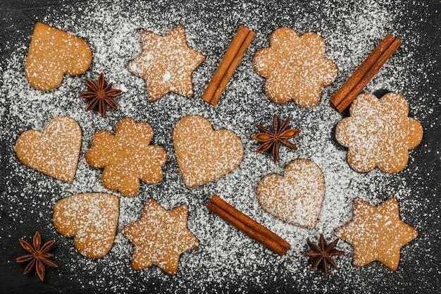 Close up cuore e a forma di stella biscotti di panpepato di natale con cannella e anice stellato spezie su sfondo nero ardesia con glassa di zucchero bianco in polvere, vista dall'alto in elevazione, direttamente sopra