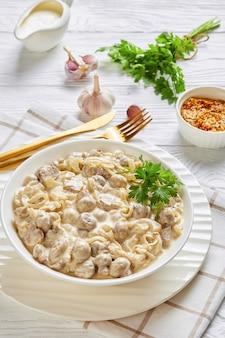 Close-up di altamente versatile pulsante cremoso salsa di funghi, champignon saltati in salsa di panna acida servita in una ciotola bianca, su un tavolo di legno, vista verticale dall'alto