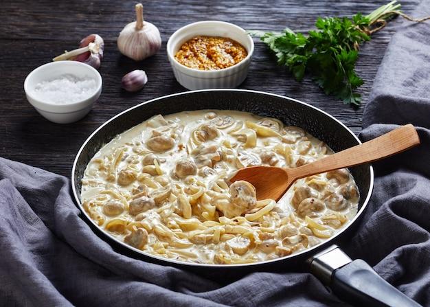 Close-up di pulsante cremoso altamente versatile salsa di funghi, champignon saltati in salsa di panna acida in una padella su un tavolo di legno scuro con ingredienti, vista del paesaggio