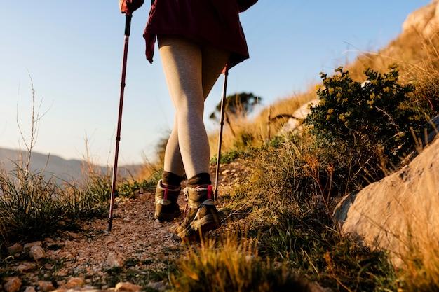 Chiuda in su escursionista con bastoni