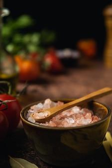 Chiuda in su dei cristalli rosa himalayani del sale su priorità bassa rustica scura